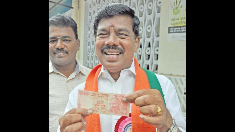 BJP candidate Karu Nagarajan displays a Rs 20 note distributed as a token for cash for vote. (Photo: DC)