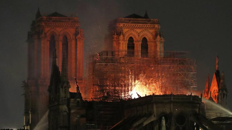 Firefighters tackle the blaze as flames and smoke rise from Notre Dame cathedral as it burns in Paris. (Photo: AP)