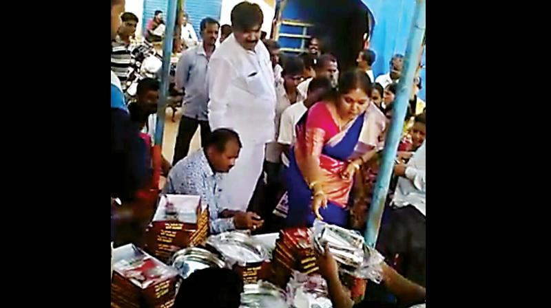 Former Bengaluru deputy mayor R Shankar and his wife distributing saris among voters of Ranibennur. (Photo: DC)