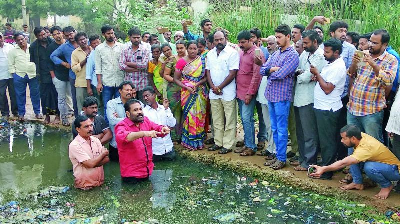 Nellore rural MLA K. Sridhar Reddy enters sewage water in protest against the official negligence in constructing a protection wall for the walkway bridge over the drainage at Chanakya puri colony in Nellore city on Wednesday.  (DC)