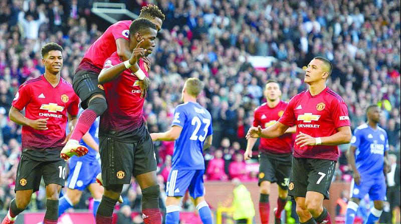 Manchester United's Paul Pogba (centre) celebrates after scoring against Leicester City in their English Premier League match at Old Trafford in Manchester on Friday. The hosts won 2-1. (Photo: AFP)