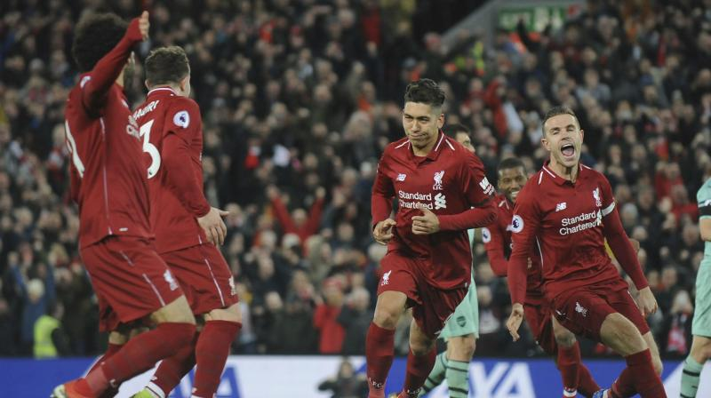 Liverpool extended their Premier League lead to nine points as Roberto Firmino's hat-trick hammered Arsenal 5-1 at Anfield, while Tottenham's title challenge crumbled in a 3-1 home defeat to Wolves. (Photo: AP)
