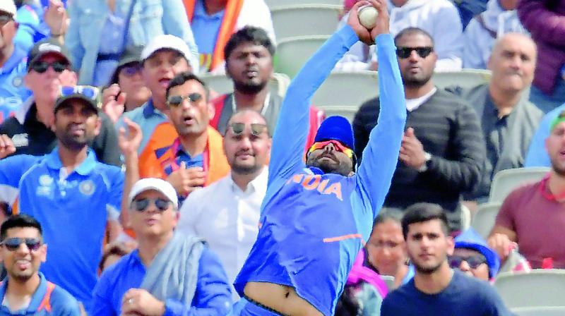 Ravindra Jadeja takes a catch to dismiss New Zealand's Tom Latham during the first semifinal at Old Trafford in Manchester, England, on Wednesday. (Photo; AFP)