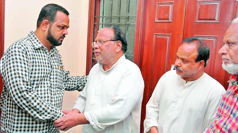 Neighbours console Mohammed Sayeed (middle) the father of Farhaj Ahsan. Ahsan died in New Zealand terror attack on Friday.