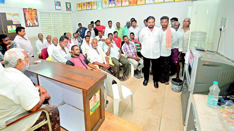 Shocked Telugu Desam partymen watch television at the party office at Narasaraopet in Guntur district on Monday for updates about their leader Kodela Siva Prasada Rao's health after the news about his suicide reached them.