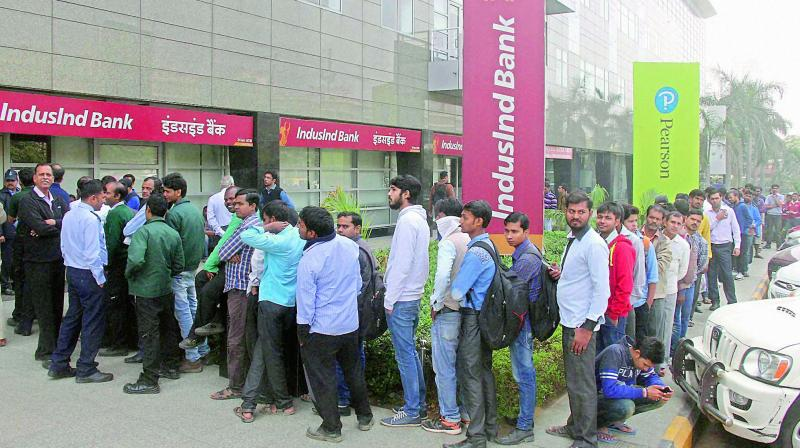People queue up outside a bank to withdraw cash. (Photo: PTI)