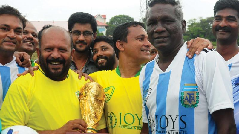 Agriculture Minister V S Sunilkumar presents a replica of FIFA world cup trophy after the exhibition match held in Thrissur on Saturday. Former Indian captain I M Vijayan is also seen.