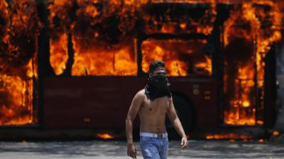 An anti-government protester walks near a bus that was set on fire by opponents of Venezuela's President Nicolas Maduro during clashes between rebel and loyalist soldiers in Caracas, Venezuela. (Photo:AP)