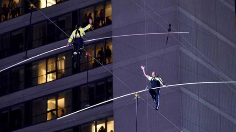 New York allowed the siblings to attempt Sunday's walk on the condition that they wear safety harnesses, a mandate Nik had said added physical weight and stress to the challenge. (Photo: AFP)