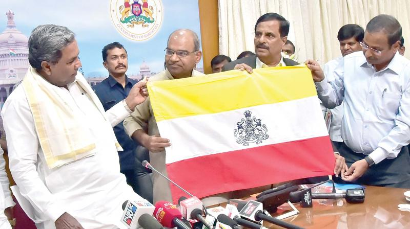 Chief Minister Siddaramaiah with Kannada Sahitya Parishat president Manu Baligar and Kannada Development Authority chairman Prof S.G Siddaramaiah among others with the proposed new Kannada Flag in Bengaluru on Thursday — DC