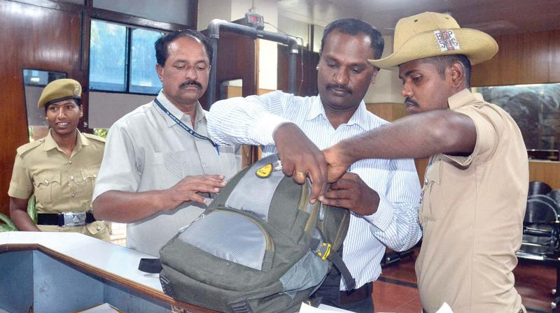 Security guards checking bags at Lokayukta office.	—DC