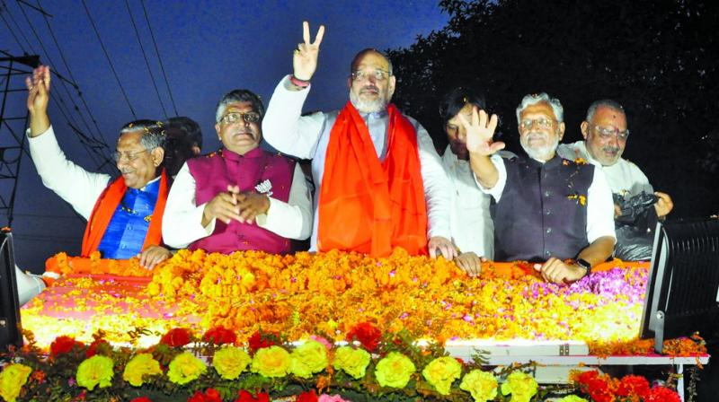 BJP president Amit Shah with Sushil Kumar Modi and party's Patna Sahib candidate Ravi Shankar Prasad during a roadshow in Patna on Saturday. (PTI)