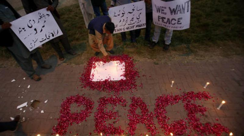 A Christian adjusts a candle next to wording 'Peace' drawn with rose petals during a candlelight vigil for the victims of an overnight attack on the Quetta Police Training Academy, in Islamabad, Pakistan. (Photo: AP)