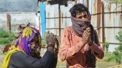 A migrant worker, suspected of coronavirus infection, and his wife beg a policeman to be allowed to go back to their native place, at a soup kitchen set up in New Delhi on March 27, 2020. (PTI)