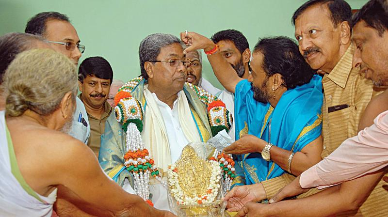 CM Siddaramaiah being greeted by Hindu priests at his home office, Krishna in Bengaluru on Wednesday