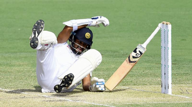 Karunaratne slumped to the ground, dropping his bat as Australian players ran to assist. (Photo: AFP)