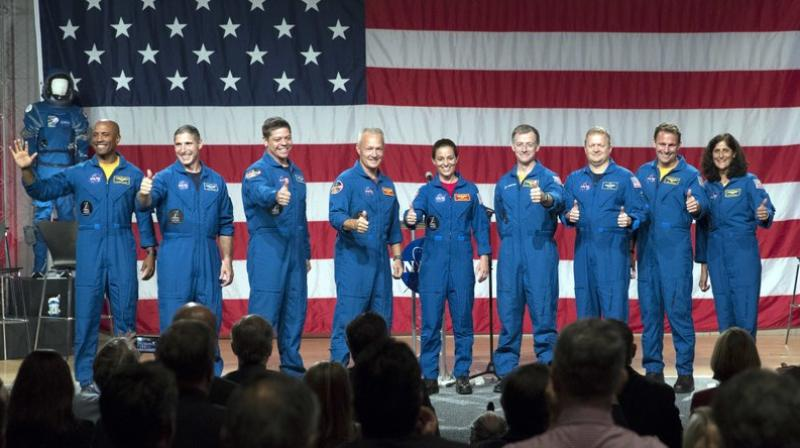Astronauts, left to right, Victor Glover, Michael Hopkins, Robert Behnken, Douglas Hurley, Nicole Mann, Christopher Ferguson, Eric Boe, Josh Cassada and Sunita Williams give a thumbs up to the crowd after NASA announced them as astronauts assigned to crew the first flight tests and missions of the Boeing CST-100 Starliner and SpaceX Crew Dragon.  (AP Photo/David J. Phillip)