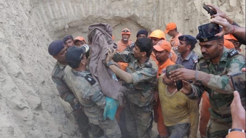 As the rescuers on Friday reached close to the spot where the child was trapped, digging by machines was stopped and was carried out manually to ensure that soil did not fall over the infant, officials said. (Image: ANI)
