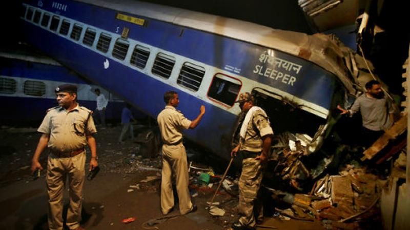 Policemen stand guard near the upturned coaches of the Kalinga-Utkal Express after an accident near Khatauli in Uttar Pradesh. (Photo: PTI)