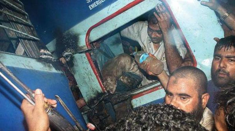 A passenger is rescued from one of the coaches of the Puri-Haridwar Utkal Express train after it derailed in Khatauli near Muzaffarnagar on Saturday (Photo: PTI)