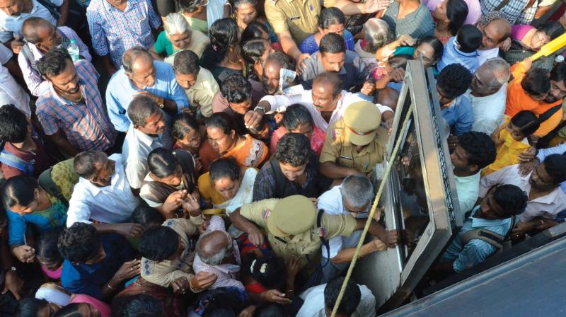 Patients rush to enter a police bus to medical college from Thiruvananthapuram Central Railway station due to the strike on  Monday. (Photo: Peethambaran Payyeri )