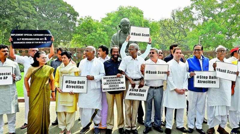 Former Congress president Sonia Gandhi stands along with Opposition party members during a protest outside Parliament during the Budget Session in New Delhi on Thursday. AICC president Rahul Gandhi and other leaders  are also seen. (Photo: PTI )