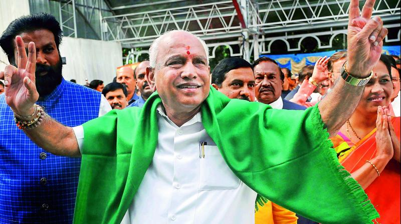 BJP leader B. S. Yeddyurappa flashes the victory sign as he arrives to take oath as Chief Minister of Karnataka in Bengaluru on Thursday