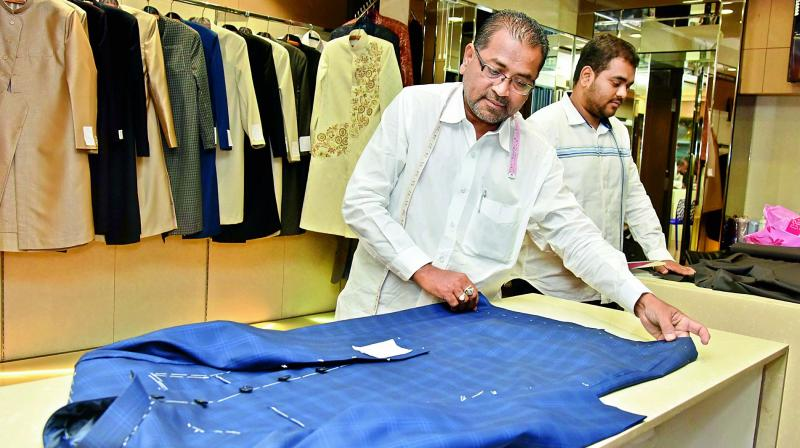 Tailors give final shape to a sherwani at a shop in the city on Thursday.  (Image: P.Surendra)