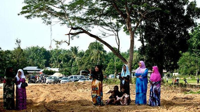 Local Malaysian women watch preparations for the re burial of remains believed to be those of ethnic Rohingya found at human trafficking camps. (Photo: AFP)