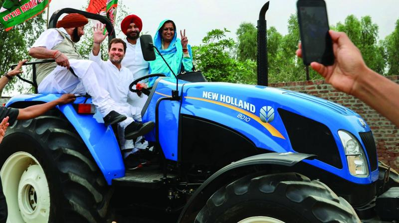 Congress chief Rahul Gandhi waves from the driver's seat of a tractor during a poll campaign in Ludhiana  on Wednesday. (Image: PTI)