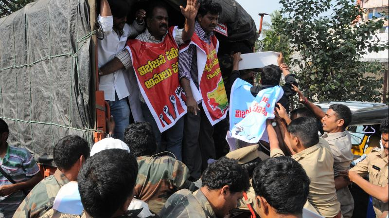 Police personnel detain Left party activists as they stage a protest in Visakhapatnam on Thursday.