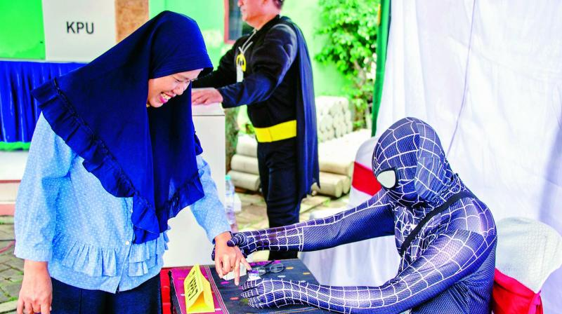 Indonesian election workers dressed in superhero costumes register voters at a polling station in Surabaya on Wednesday. Indonesia kicked off one of the world's biggest one-day elections, pitting president Joko Widodo against ex-general Prabowo Subianto in a race to lead the Muslim-majority nation. (Photo:  AFP)