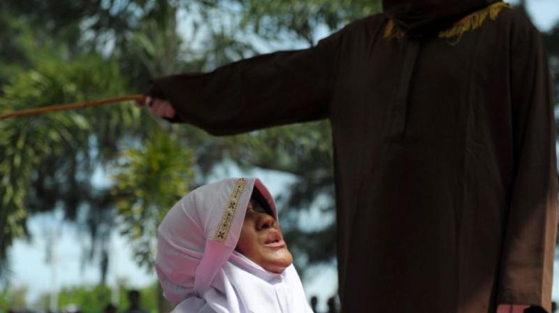 A religious officer canes a woman for spending time in close proximity with a man who is not her husband in Banda Aceh, Indonesia, on November 28, 2016. (Photo: AFP)