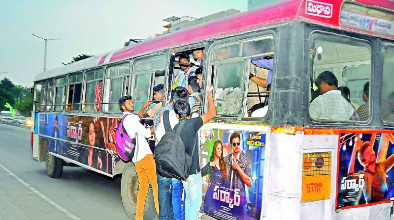 An overcrowded bus is seen in the city with college-going students dangerously hanging out of the rear door. (Photo:P. SURENDRA)