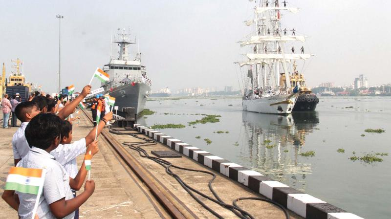 School children wave the national flag to welcome INS Tarangini returning to Kochi after Lokayan-18