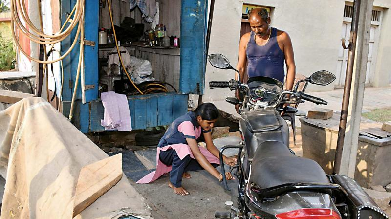 Belagavi: State arts topper Kusuma Ujjini fixing a flat tyre at her father's shop in Kottur. She helps her father Devendrappa in her spare time. Kusuma, who studied at Indu Independent PU College in Kottur, Belagavi, scored 594 out of 600 marks in the second PUC exam.