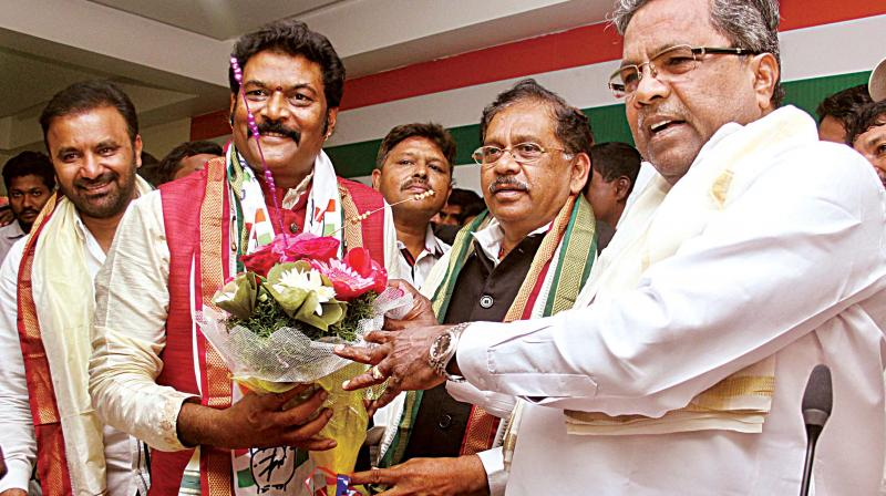 Hosapete MLA Anand Singh is greeted by Chief Minister Siddaramaiah and KPCC chief Dr G. Parameshwar after he joined the Congress, in Bengaluru on Wednesday. (Photo: DC)