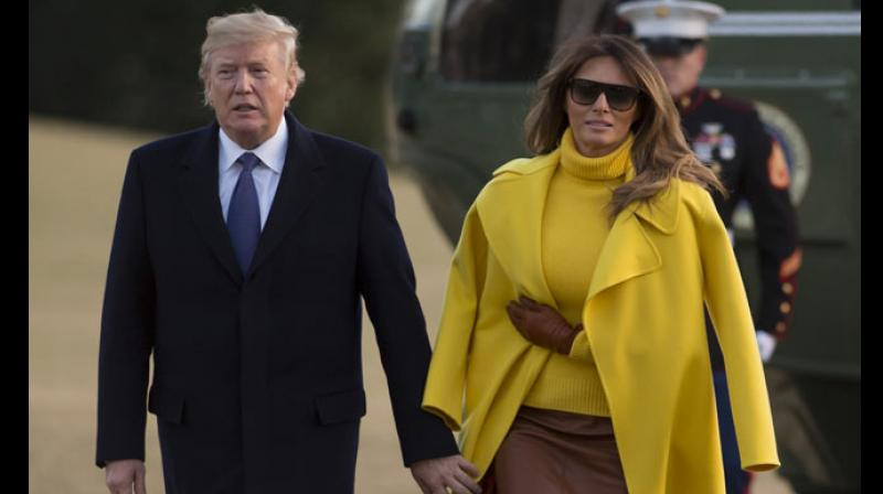 Melania's long yellow overcoat is deceivingly draped over her shoulders leading the President to mistakenly grab her sleeves instead of her hand. (Photo: AFP)