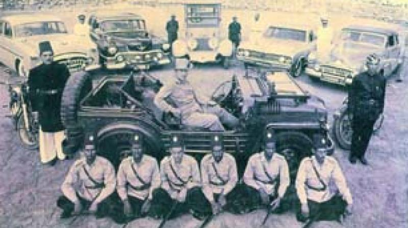 Prince Mukarram Jah with cars and attendants (circa 1965)