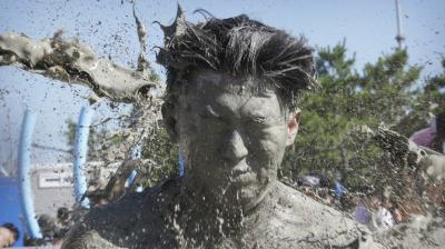 The 21st annual mud festival features mud wrestling and mud sliding. (Photos: AP)