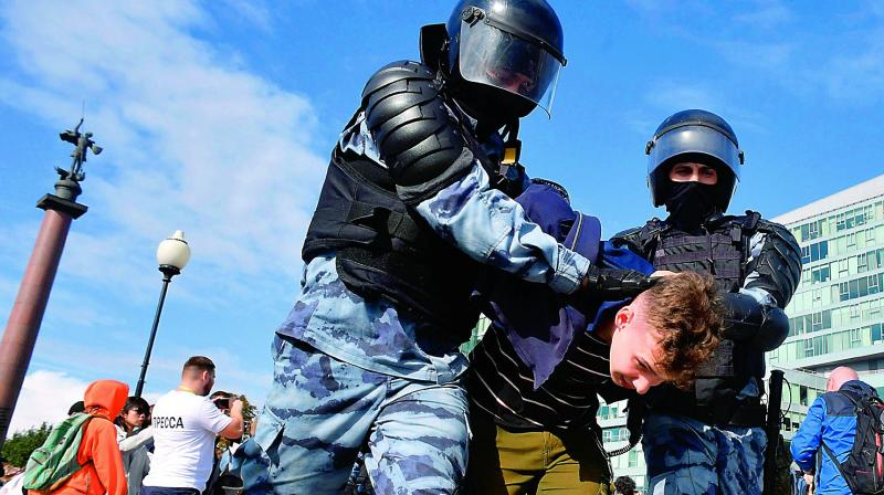 Servicemen of the Russian National Guard detain a participant of an unsanctioned rally urging fair elections in Moscow on Saturday.  	— AFP