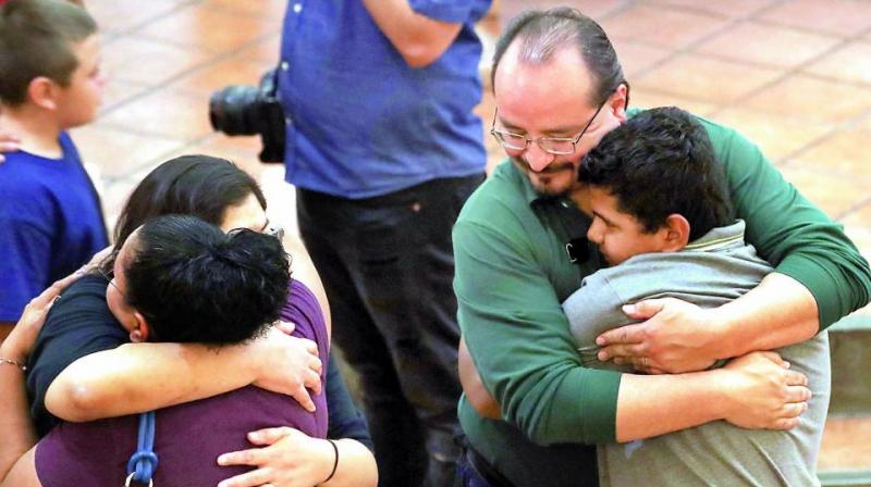 People hug at St Pius X Church at a vigil for victims after a mass shooting which left at least 20 people dead on Sunday in El Paso, Texas. (Photo: AFP)