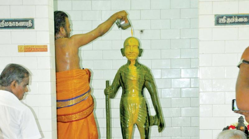Sandal paste being poured on the statue of Mahatma Gandhi at the temple. (Photo: DC)