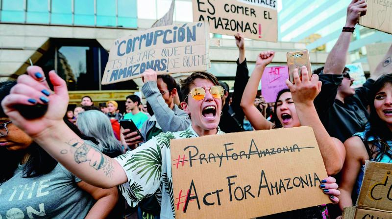 Activists demonstrate during a protest against Brazil's President Jair Bolsonaro over the fires in the Amazon rainforest in front of Brazil's Embassy in Santiago on Saturday. (Photo: AFP)