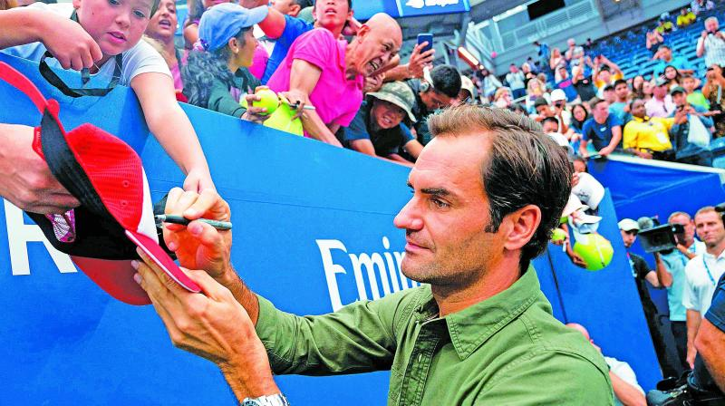 Roger Federer obliges autograph hunters during a training session ahead of the US Open. (Photo: AFP)