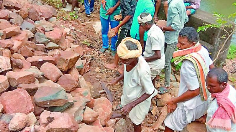 File picture of villagers strengthening a road with boulders in old Adilabad district. The road was was washed away due to the rains. (Photo: DC)