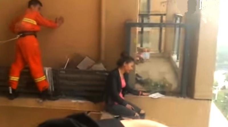 Video: Firefighter risks his life to stop woman from jumping