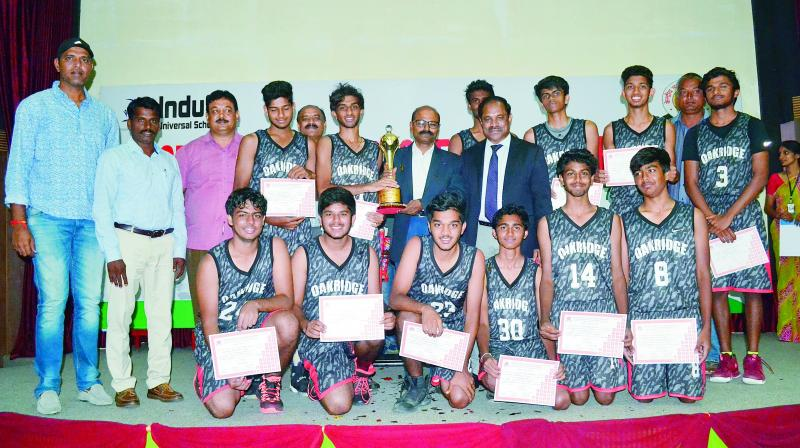 Oakridge International School's Under-19 basketball players are all smiles as they pose with the CBSE Cluster VII Basketball winner's trophy from A. Dinakar Babu, Vice-Chairman & Managing Director of Sports Authority of Telangana State, at the Indus Universal School in Yapral, Secunderabad.