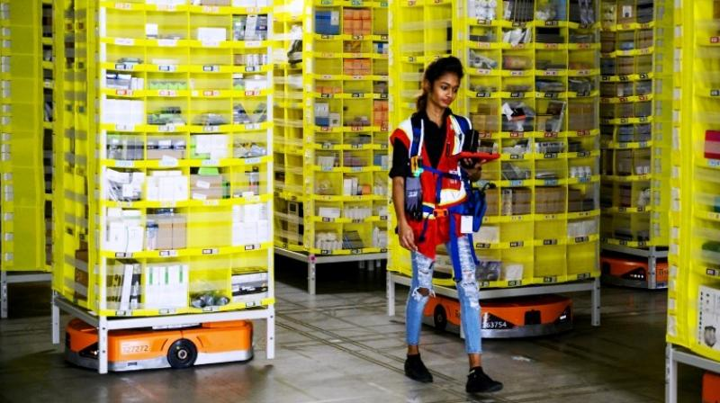 Amazon employee Deasahni Bernard moves among robots at the 855,000-square-foot Amazon fulfilment centre in Staten Island. (Photo: AFP)