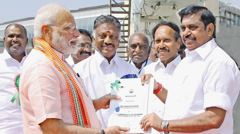 Chief Minister Edappadi K. Palaniswami presenting a memorandum to Prime Minister Narendra Modi at the Madurai airport on Monday. Deputy Chief Minister  O. Panneerselvam is also seen. (DC)